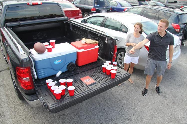 The back of a truck filled with drinks and two people pointing at it