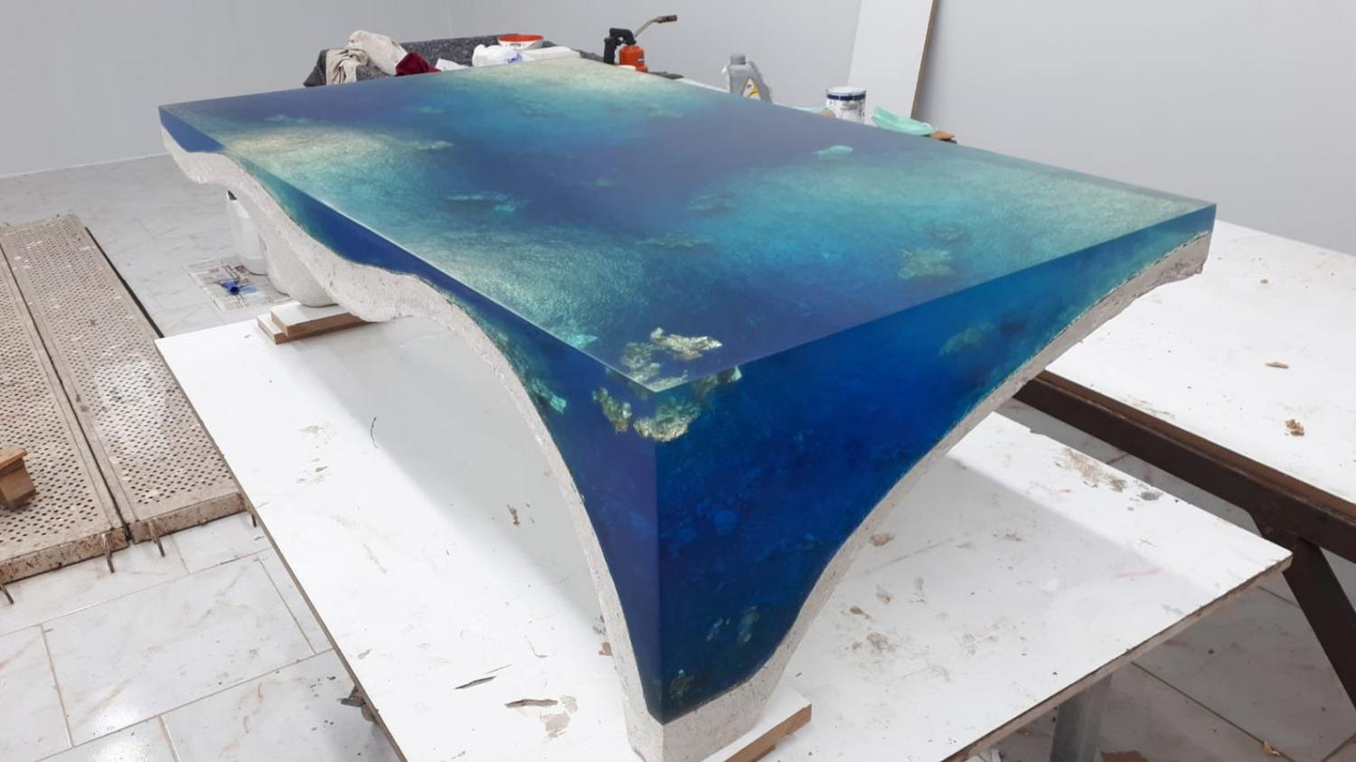 luxury table is a concrete sculpture and filled with epoxy to give stunning illusion of looking into a deep dark blue sea