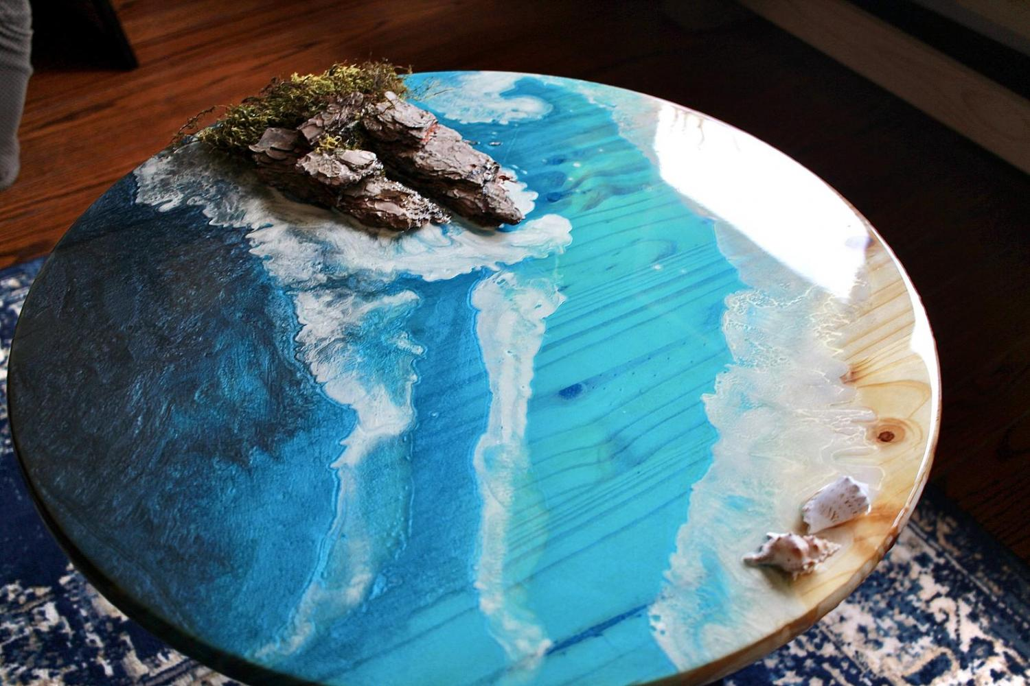 A circular epoxy table made to look like the shore of an ocean