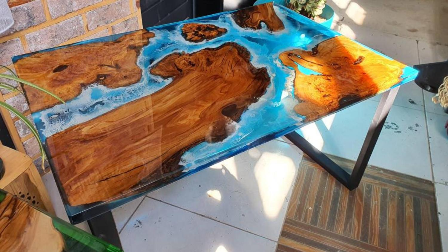A similar epoxy table with bright blue waters surrounding islands made from olive wood