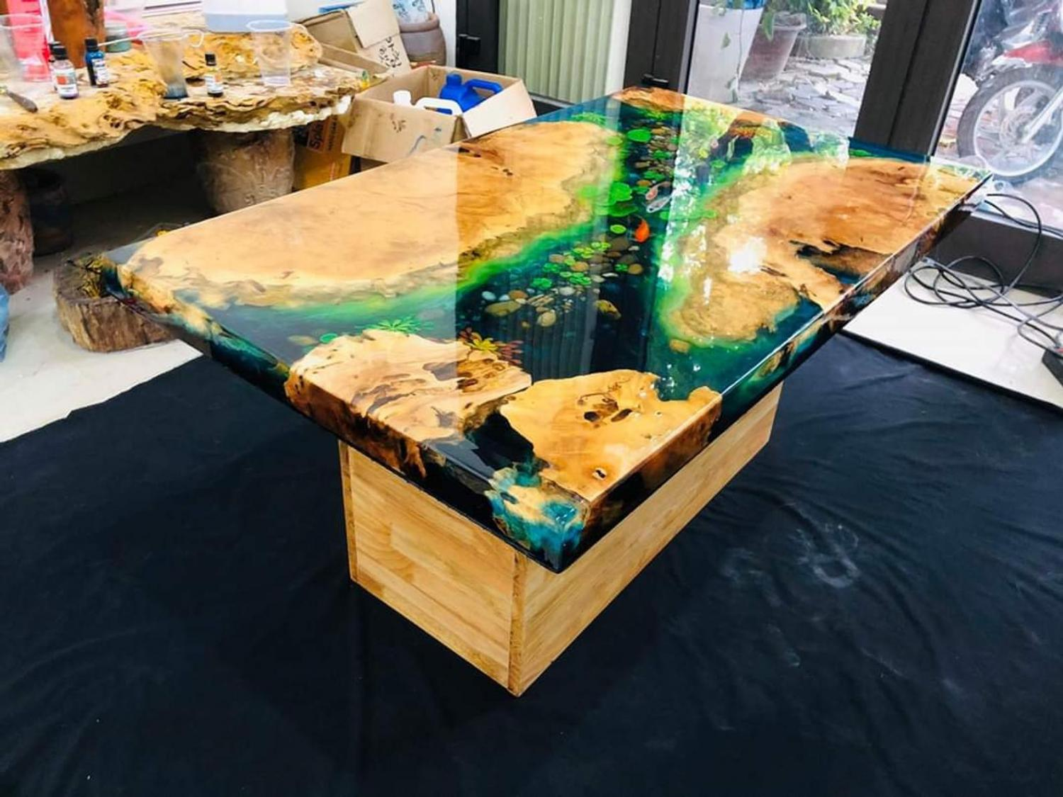amazing epoxy table is made to look like a koi pond with what looks like real fish swimming around inside the water
