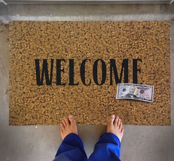 the 50 dollar bill welcome mat is a door mat with a photo realistic fake 50 dollar bill on it so that the people that come to your door selling vacuum